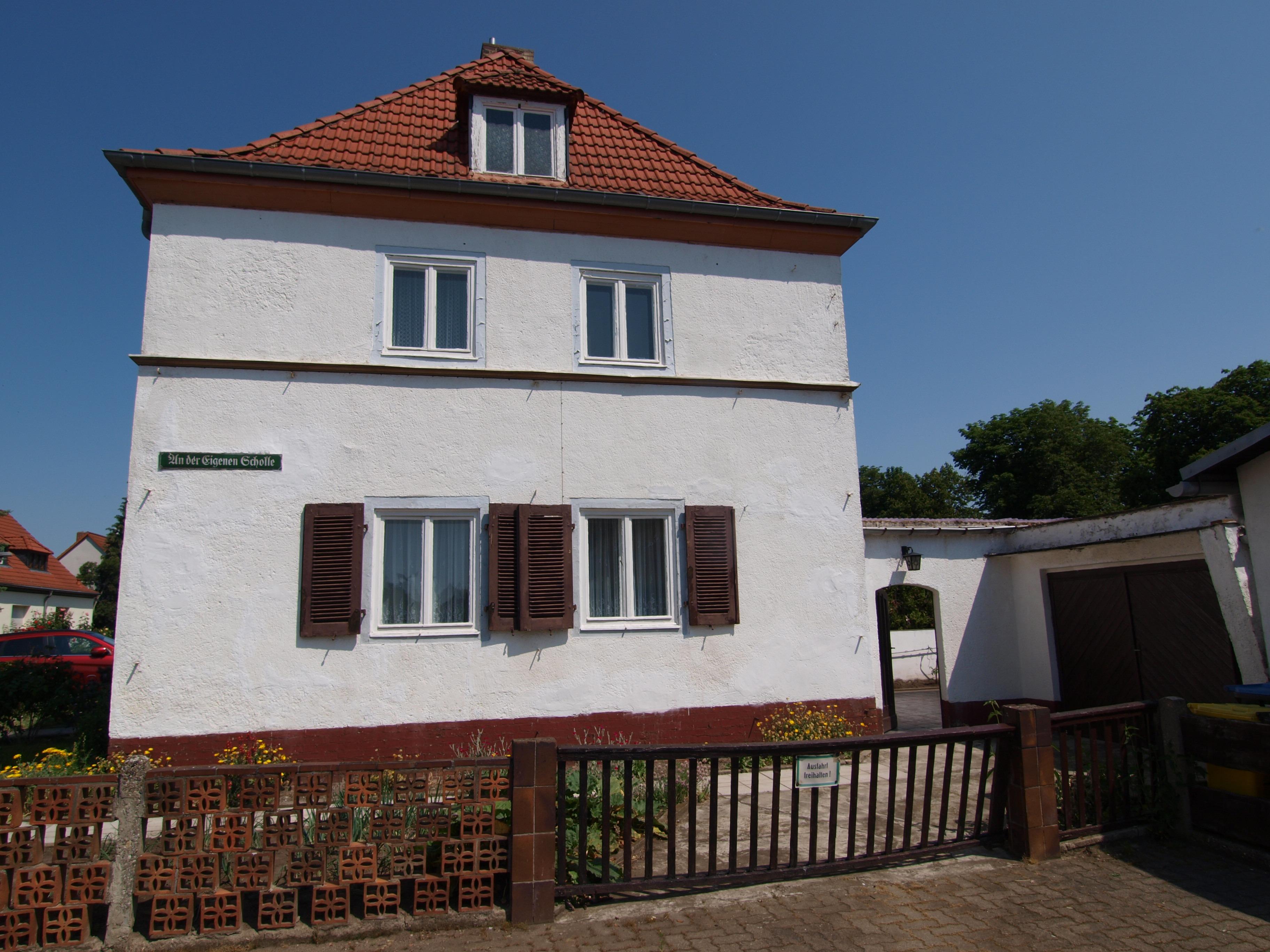 Einfamilienhaus - Hausansicht mit Garage und Zugang zum Garten